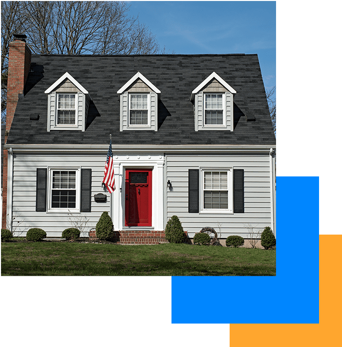 House in Iowa with a dark grey shingle roof, white siding, a red door, and an American flag hanging