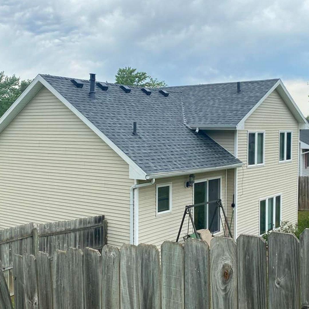 Urbandale, IA house with a gyre shingle roof and light beige siding