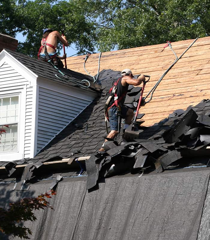 Roofers replacing a black shingle roof